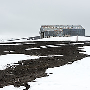 An aircraft hangar sits abandoned at the former whaling station at Whalers Bay on Deception Island. Deception Island, in the South Shetland Islands, is a caldera of a volcano and is comprised of volcanic rock.