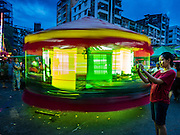 29 OCTOBER 2015 - YANGON, MYANMAR: A woman takes a picture with her smart phone while a human powered Merry Go Round spins behind her during a street carnival in central Yangon. Electricity is scarce in Myanmar, especially in rural areas, and most traveling carnivals use human powered rides. Workers climb to the top of the Ferris Wheel and then pull it around getting it spinning. They do the same with Merry Go Rounds, but instead of climbing to the top they pull it around. The carnival coincided with the Thadingyut Festival, the Lighting Festival of Myanmar, which is held on the full moon day of the Burmese Lunar month of Thadingyut, October or November on the Gregorian calendar. The carnival featured food, rides and games.      PHOTO BY JACK KURTZ