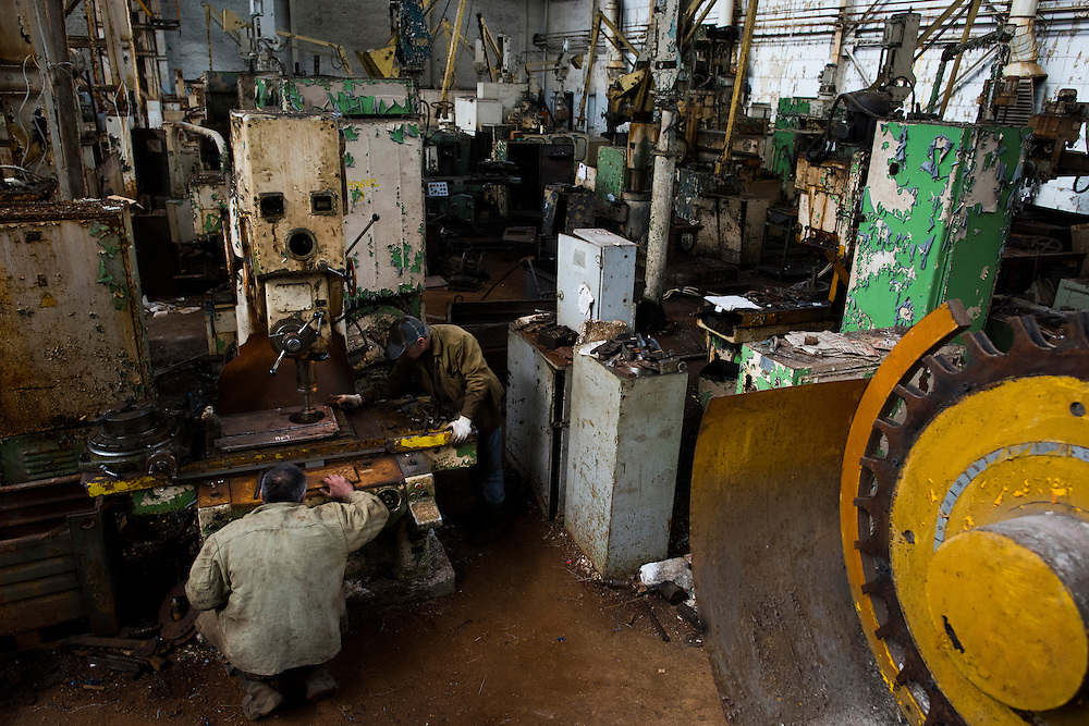 Members of Azov Engineering Group use one of the few working tools in a sea of abandoned machines on September 9, 2015 in Kyiv, Ukraine.