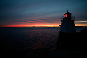 USA, Newport, RI - Castle hill light house shines it's red light out to sea at the mouth of Narragansett bay with a fading sunset on the horizon.