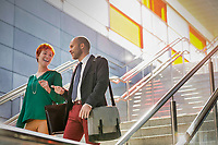Portrait of businessman and businesswoman talking while walking down stairs