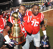 Ole Miss Rebels linebacker Keith Lewis (24) and Ole Miss Rebels offensive lineman Daronte Bouldin (76) carry the Golden egg from the field following the win over Mississippi State at Vaught-Hemingway Stadium in Oxford, Miss. on Saturday, November 29, 2014. Ole Miss won 31-17.
