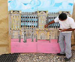 © Licensed to London News Pictures. 29/05/2012, Lashkar Gah, Afghanistan. A chef working for the British military in Afghanistan puts the finishing touches to a painting of Buckingham Palace as he prepares decorations for a street party in the military base.  Photo credit : Alison Baskerville