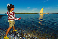 Girl skipping stones across the water with the Schooner Nathaniel Bowditch moored behind, Russ Island, Penobscot Bay, Maine USA