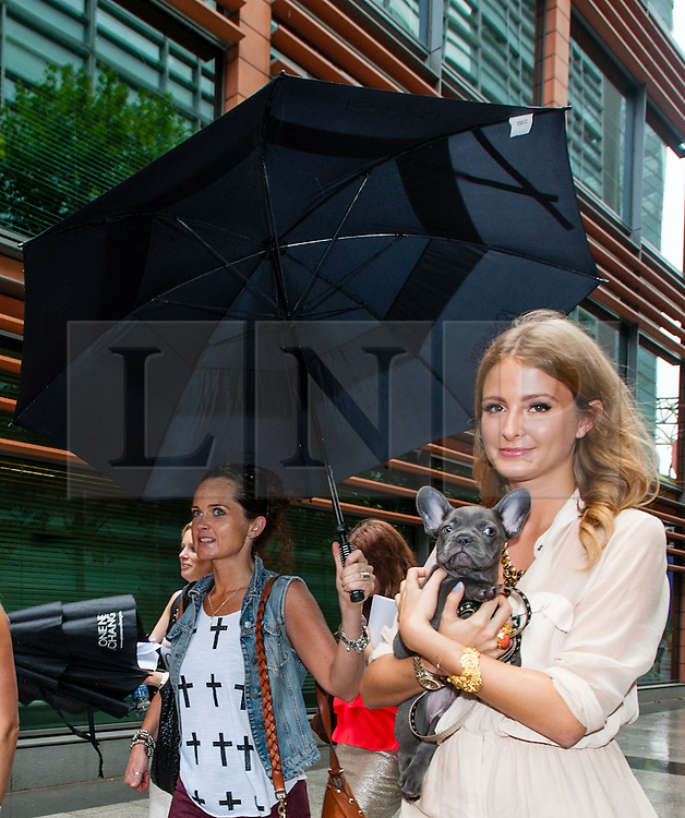 © Licensed to London News Pictures. 19/08/2012. London,UK.  Millie Mackintosh, of reality TV show Made in Chelsea, braves the rain and participates in exclusive fundraising walk The Sunday Strut, in aid of The Princes Trust. Here she carries her pet dog Herbie.  Photo credit : Richard Isaac/LNP