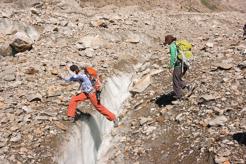 Two women ski mountaineers jumping a crevasse on the Biafo glacier in the Karakoram mountains of Pakistan