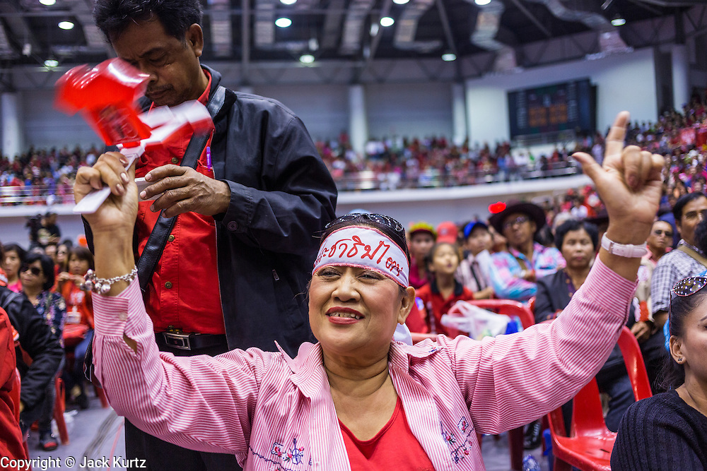"""23 FEBRUARY 2014 - NAKHON RATCHASIMA (KORAT), NAKHON RATCHASIMA, THAILAND: A woman cheers for Red Shirt speakers in Korat. The United front of Democracy against Dictator (UDD or Red Shirts), which supports the elected government of Yingluck Shinawatra, staged the """"UDD's Sounding of the Battle Drums"""" rally in Nakhon Ratchasima (Korat) to counter the anti-government protests that have gripped Bangkok since November. Around 4,000 of UDD's regional and provincial coordinators along with the organization's core members met at Liptapunlop Hall inside His Majesty the King's 80th Birthday Anniversary Sports Complex in Korat to discuss the organization's objectives and tactics against anti-government protestors, which the UDD says """"seek to destroy the country's democracy."""" The UDD leadersa announced that they will march to Bangkok and demonstrate against anti-government protests led by Suthep Thaugsuban.   PHOTO BY JACK KURTZ"""