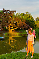 Old Westbury, New York, U.S. 22nd June 2013. Standing by the pond at dusk, MORGAN, 9, of East Islip, is one of many young girls wearing fairy costumes at the Midsummer Night event at Old Westbury Gardens, on the grounds of the historic Long Island Gold Coast estate.