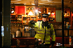 © Licensed to London News Pictures. 24/02/2016. London, UK. A Police officer gestures from insideBella Italia restaurant in Leicester Square, London where a man claiming to be in possession of a knife was holding a woman against her will in a hostage situation. Metropolitan Police reported the incident is not terrorist-related. Photo credit: Tolga Akmen/LNP