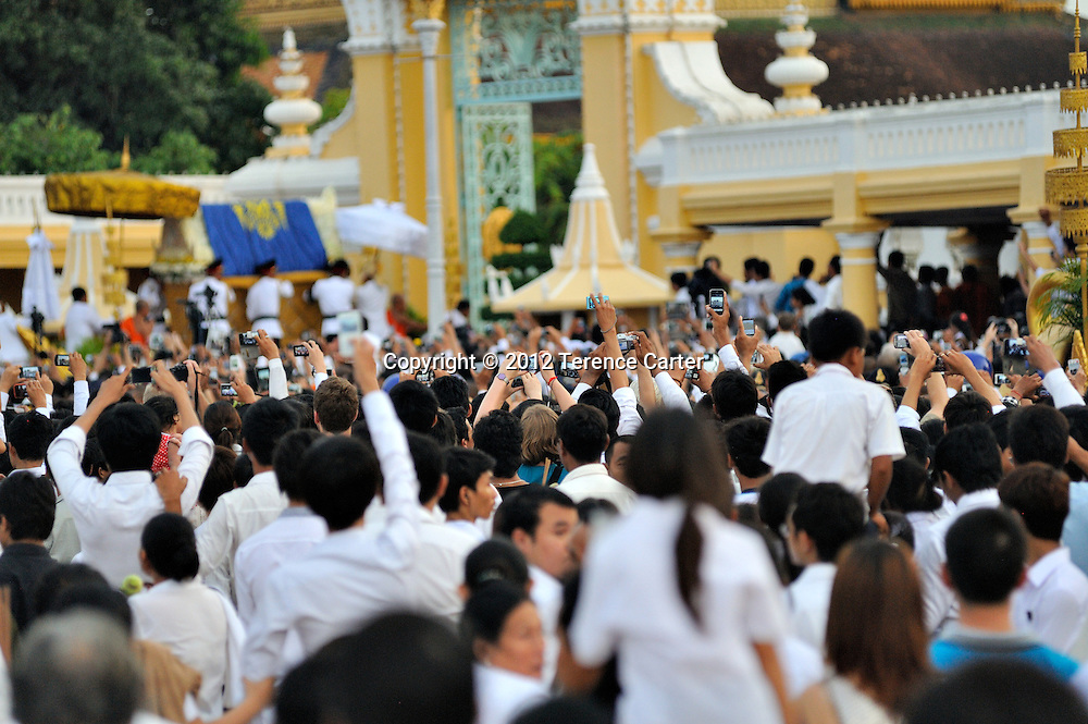 Mourners try to capture a photograph of the arrival of King Father Norodom Sihanouk's body to the Royal Palace, Phnom Penh, starting a week of mourning in Cambodia.