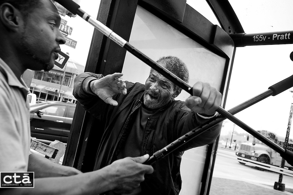 "Michael Frazier fends off the attack of another man, whom he told ""I don't like you"" just moments before, at a downtown bus stop. The 62-year old had been waiting for a Circulator bus near Baltimore's Inner Harbor before they tried hitting each other with their canes. The free bus service has been beset by issues involving intoxicated and vagrant individuals, and is considering charging to make up for a funding shortfall."