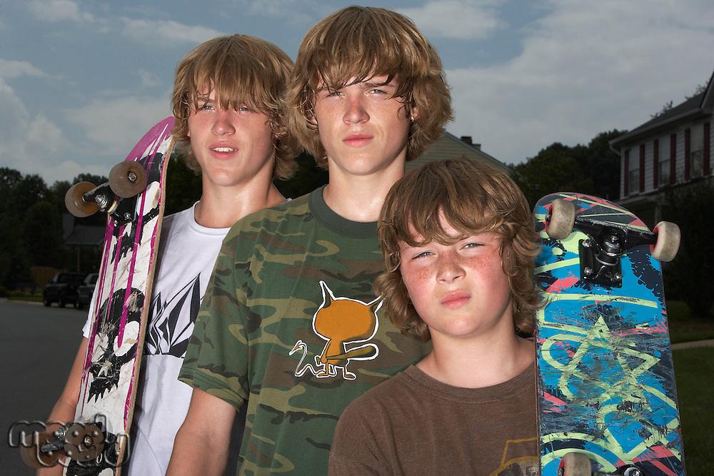 Three teenage brothers (13-17) standing on street holding skateboards portrait