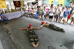 61396081<br /> Penitents lie on the ground to pray during a Holy Week ritual to atone for their sins, on a street in Mandaluyong City, the Philippines, Thursday, 17th April 2014. Picture by  imago / i-Images<br /> UK ONLY
