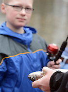 Jake Haney, 9, or Warminster, Pennsylvania watches as Patrick Haney holds a fish caught by Jake on the first day of trout season at Fanny Chapman Pond Saturday April 2, 2016 in Doylestown, Pennsylvania.  (Photo by William Thomas Cain)