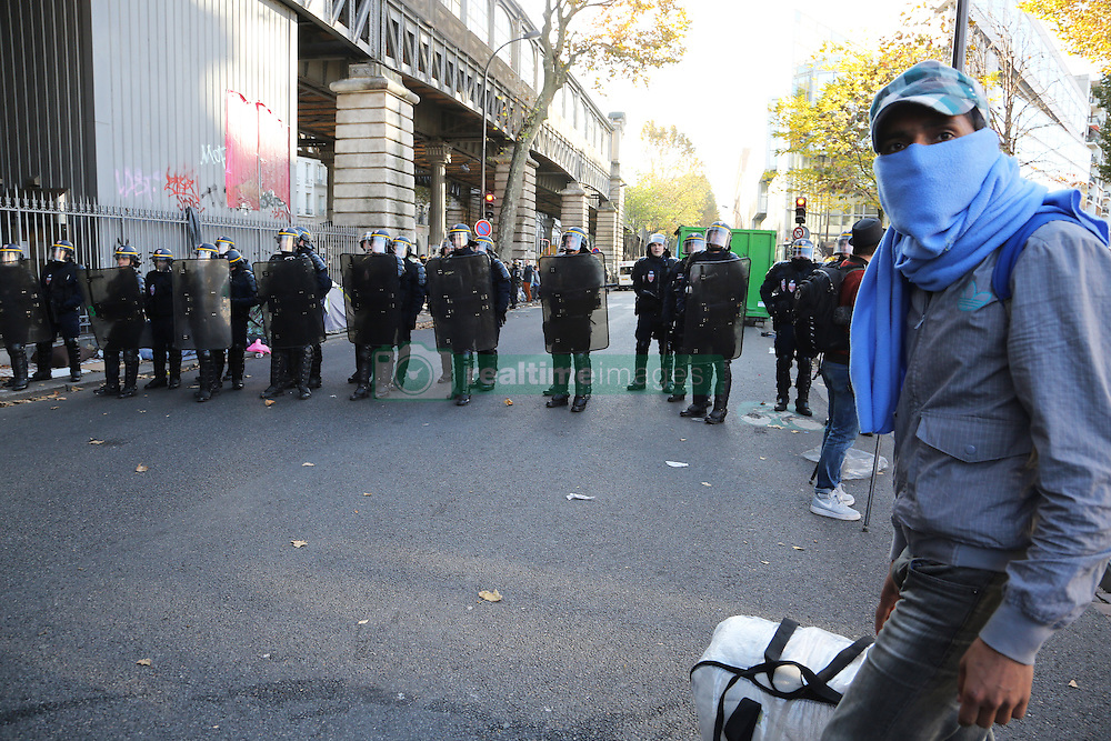 """French anti-riot policemen stand in front of migrants near the Jaures and Stalingrad metro stations, in northern Paris, France, on October 31, 2016, during a police operation aiming at a future evacuation of a migrant camp. An operation of """"administrative control"""" was underway on early October 31 in the Jaures/Stalingrad quarter before a future evacuation, whose date has not yet been set, according to a police source. The makeshift camp on the outskirts of the 10th and 19th arrondissements in the north of the capital numbers today 2,500 people, according to the City of Paris. Photo by Somer/ABACAPRESS.COM"""