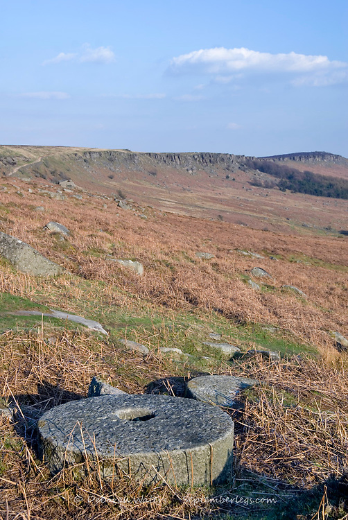 Millstone lying abandoned in situ at the old quarry site at Stanage Edge, Peak District, UK