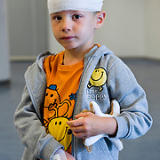 Nederland Rotterdam 25-08-2009 20090825 Foto: David Rozing ..Serie over zorgsector, Ikazia Ziekenhuis Rotterdam. Jong kind heeft als troost een verband gekregen, het kind is zojuist besneden dus het verband is voor de show.  Young child boy with bandages, these are fake, the boy has been circumciced and the fake bandage are meant to cheer him up. Holland, The Netherlands, dutch, Pays Bas, Europe, verband, verbonden, hoofdwond, gaas, gaasje, wondbedekker, verbandgaas, verbandgazen, vulnerable, knuffel, smiley, smileys, tegenstelling, contrast, positief blijven, positiviteit, ventje..Foto: David Rozing genezen, genezing, ziekte bestrijding,, ziektekosten,,zorgverlening