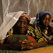 Latifatou Ouedraogo (10) with her grandmother, Zarata Ouedraogo (approximately 70), under the mosquito net they share in the village of Songodin in the Sanmatenga region of Burkina Faso on 25 February 2014. Mosquito nets greatly decrease the incidence of malaria by reducing the risk of being bitten by the nocturnal Anopheles mosquito, which carries the malaria parasite.