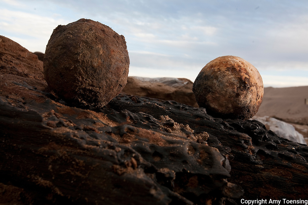 ORANJEMUND, NAMIBIA -- SEPTEMBER 24: An iron ball, used to sink the ship, and a stone canon ball, used as anti-personal, found on site of the wreck on September 24, 2008 in Oranjemund, Namibia. The wreck was discovered by miners in the Namdeb diamond mine off the coast of Namibia. The ship was found seven meters below sea level on April 1, 2008. Archeologists presume the wreck is from the early 1500s. Most of the the artifacts found are being stored in a storage shed at the Namdeb Diamond Mine. Items include: copper ingots, bronze canons, canon balls, pewter bowls and plates, ivory tusks from African elephants, and most substantial over 2000 gold coins- approximately 21 kg - the most gold found in Africa since the Valley of the Kings in Egypt. (Photo by Amy Toensing) _________________________________<br />