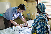 Dr Peter O'Reilly attends to a patient on the Intensive care ward during the daily rounds. <br /> St Walburg's Hospital, Nyangao. Lindi Region, Tanzania.
