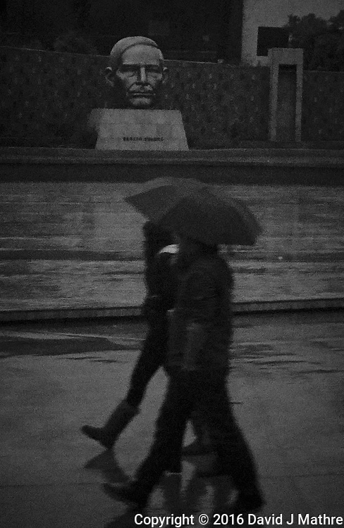 Walking in the rain at the Ensenada Cruise Terminal. Image taken with a Nikon N1 V3 camera and 10-30 mm lens (ISO 1600, 10 mm, f/3.5, 1/250 sec). Raw image processed with Capture One Pro (including conversion to B&W).