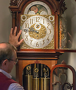 "© Licensed to London News Pictures. 23/10/2014. Guidford, UK. Michael Tooke changes one of his favourite clocks in the shop. As British Summer Time comes to an end, staff at Horological Workshops start the task of changing the 100's of clocks at their store in Guildford, Surrey, UK. Michael Tooke who has owned the store for over 40 years and worked in the clock business all his life said. ""at this time of year we get a lot of people who bring clocks in for repair after they have changed the time incorrectly by winding back the hands manually"". Clocks change on Sunday morning 26th October. Photo credit : Stephen Simpson/LNP"