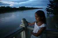 A young girl looks out along the Arauca River, which borders Colombia and Venezuela, from the Colombian city of Arauca on June 27, 2009. The border region between Colombia and Venezuela has often been a region with a high level of activity of illegal armed groups. (Photo/Scott Dalton)