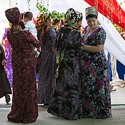 Women gather at the front of a bride's house awaiting the arrival of the groom's family car to collect the bride for the wedding, Ashgabat