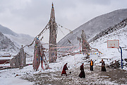 Buddhist monks play basketball on a court in their mountainside monastery in Zado, Tibet (Qinghai, China). Despite the light covering of snow, the monks report increasingly warmer winter temperatures each year and a general reduction in quanitites of fresh water on the Tibetan plateau.