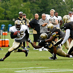 August 3, 2010; Metairie, LA, USA; New Orleans Saints running back Reggie Bush (25) runs away from defenders during a training camp practice at the New Orleans Saints practice facility. Mandatory Credit: Derick E. Hingle