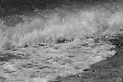 Waves are battered by offshore breezes on Oahu's North Shore, leaving trails of sea spray across the ocean's surface