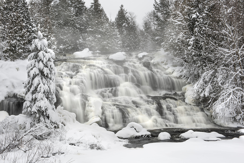 A misty Bond Falls surrounded by new fallen snow.