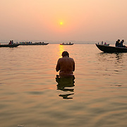 Bathers in the Ganges early in the morning, while the rowboats filled  with tourists cross nearby.