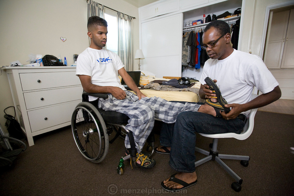 Filipe Adams, an Iraqi war vet at home with his father, who is helping him get dressed, in Los Angeles, California. (Felipe Adams is featured in the book What I Eat: Around the World in 80 Diets.) Felipe was shot in Baghdad while serving his second tour of duty in September of 2006 and his spine was shattered leaving him unable to feel his lower body, although he is still wracked with periodic pain. MODEL RELEASED.