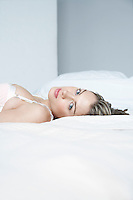 Young woman in underwear lying on bed close-up