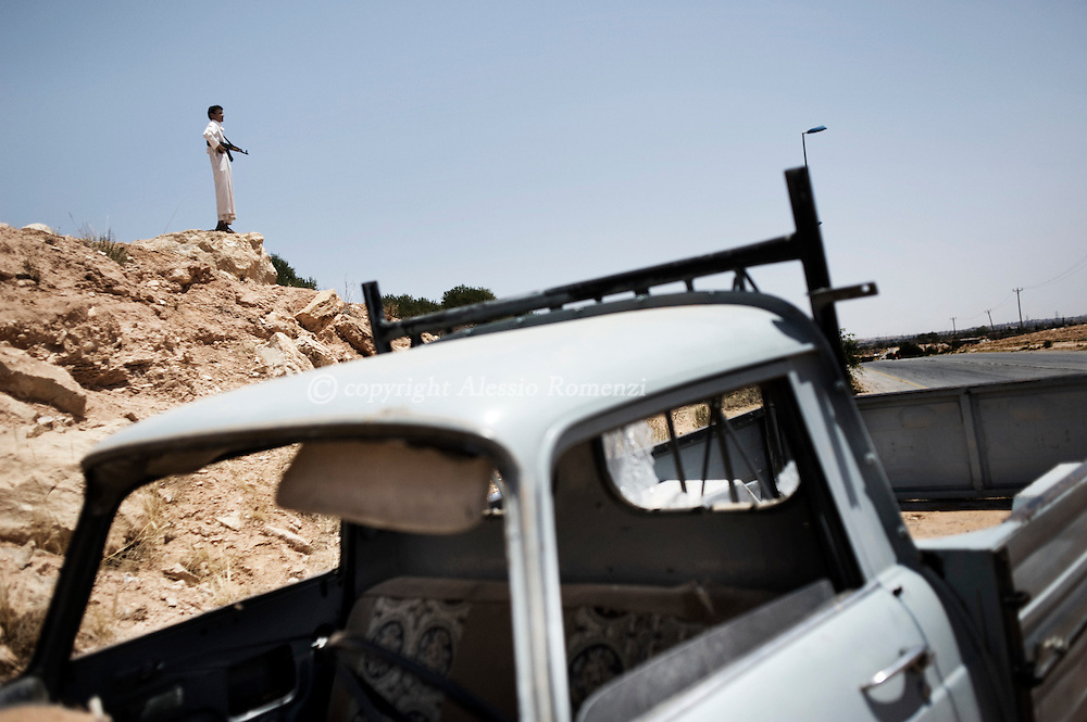 LIBYAN ARAB JAMAHIRIYA, Kikla : A Libyan rebel takes position at a checkpoint next to a main road leading to the last defensive position near the hill village of Kikla, southwest of Tripoli, during an offensive by forces loyal to Moamer Kadhafi on July 13, 2011. ALESSIO ROMENZI