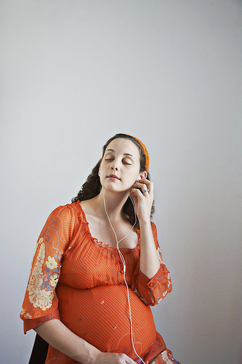 Pregnant woman listening with ear phones to music or books on tape looking very relaxed and serene
