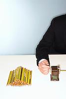 Businessman Sharpening Lots of Pencils