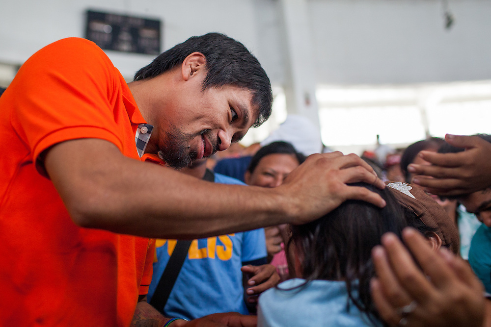 Manny Pacquiao greets a girl in the crowd inside the Tacloban City Astrodome Convention Center.<br /> <br /> Manny Pacquaio visits victims of Typhoon Yolanda in Tacloban City.  Leyte, Philippines  December 2, 2013