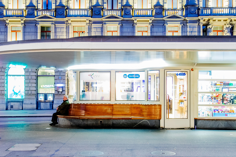 A man waits for the tram at the station on Paradeplatz in Zurich. In the background is the headquarters of the Swiss bank Credit Suisse. <br />