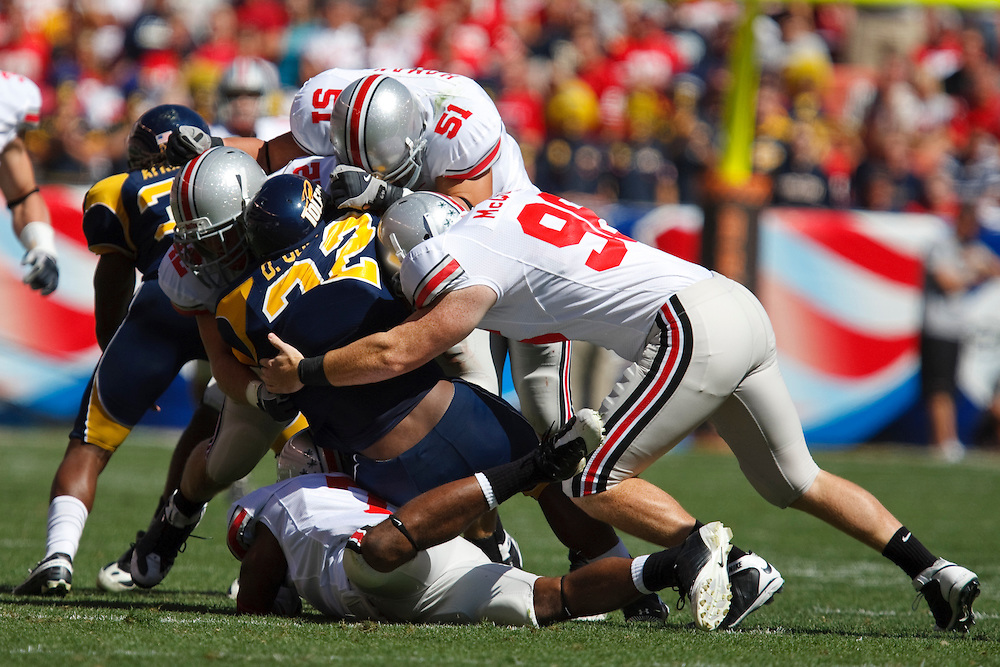 19 September 2009:   #22 Collins, DaJuane of the Toledo Rockets is tackled by #96 McQuaide, Jake of the Ohio State Buckeyes  and #51 Homan, Ross of the Ohio State Buckeyes  during the NCCA football game between Ohio State Buckeyes and the Toledo Rockets at Cleveland Browns Stadium in Cleveland, Ohio. OSU defeated Toledo 38 - 0.