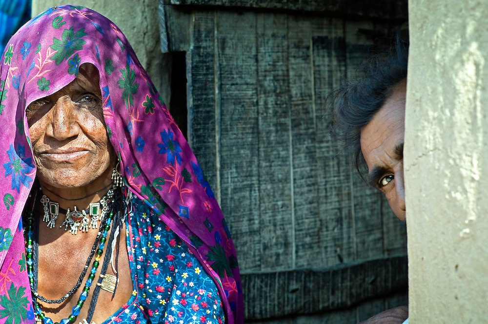Old woman from Rajasthan in front of her house where her son-in-law hides behind her (India)