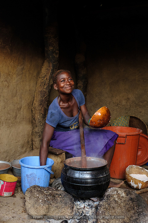 Katherine Bapuurbaala cooking a breakfast of millet porridge for the 10 residents of the family homestead she occupies in the village of Lyssah in the Upper West region of Ghana.