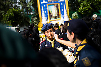 BANGKOK, THAILAND - October 26, 2017: Young boy scouts hold offerings for mourners near a large image of the late king in Bangkok, Thailand. Hundreds of thousands of people, dressed in black, have gathered in Bangkok over a year after the death of Thailand's popular King Bhumibol Adulyadej.  The five-day royal cremation ceremony is taking place between October 25-29 in Bangkok's historic Grand Palace and the Sanam Luang area.