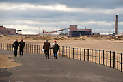 An elderly couple and a middle aged couple walk along the promenade alongside the beach at Redcar in the North East of England with an industrial plant in the background.