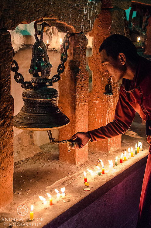 A monk rings a prayer bell during the full moon celebrations, Bodhnath stupa, Nepal