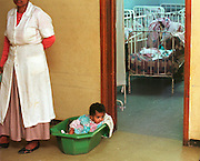 1/5/01 -- (PHOTO BY MIKE FENDER) w/ story, slug: AFRICA, file: 62040 // A baby sits in a plastic tub under the watch of a foster mom during a visit by Cheryl Carter-Shotts to the Kebebe Tsehay orphanage in January to identify children for adoption.