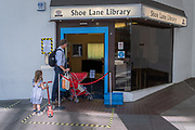 A father and his young children wait to safely enter Shoe Lane Library during the Coronavirus pandemic in the City of London, the capital's financial district, on 6th August 2020, in London, England.