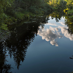 Summer clouds reflect in Wytipitlock Stream in the Reed Plantation in Reed, Maine.