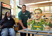 Eric LeGrand, left, SUBWAY Famous Fan and former Rutgers football player, looks on as Anthony Barr, 2014 draft prospect and newest SUBWAY Famous Fan, unveils a life-size food statue made of fresh vegetables, Wednesday, May 7, 2014, in New York. Barr joins a roster of fellow Famous Fans that include Robert Griffin III, Justin Tuck, Russell Westbrook, Pele and Michael Phelps. (Photo by Diane Bondareff/Invision for SUBWAY/AP Images)